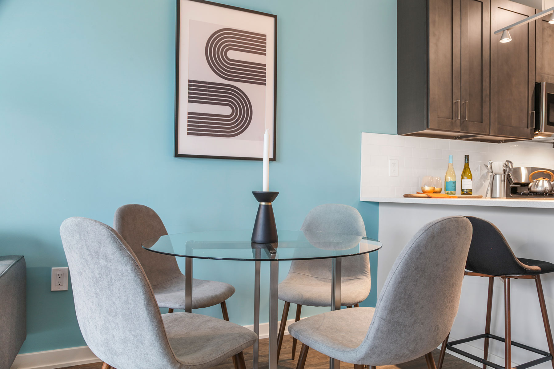 Detail of eat in glass table with 4 chairs near kitchen, light teal accent wall and wood floors