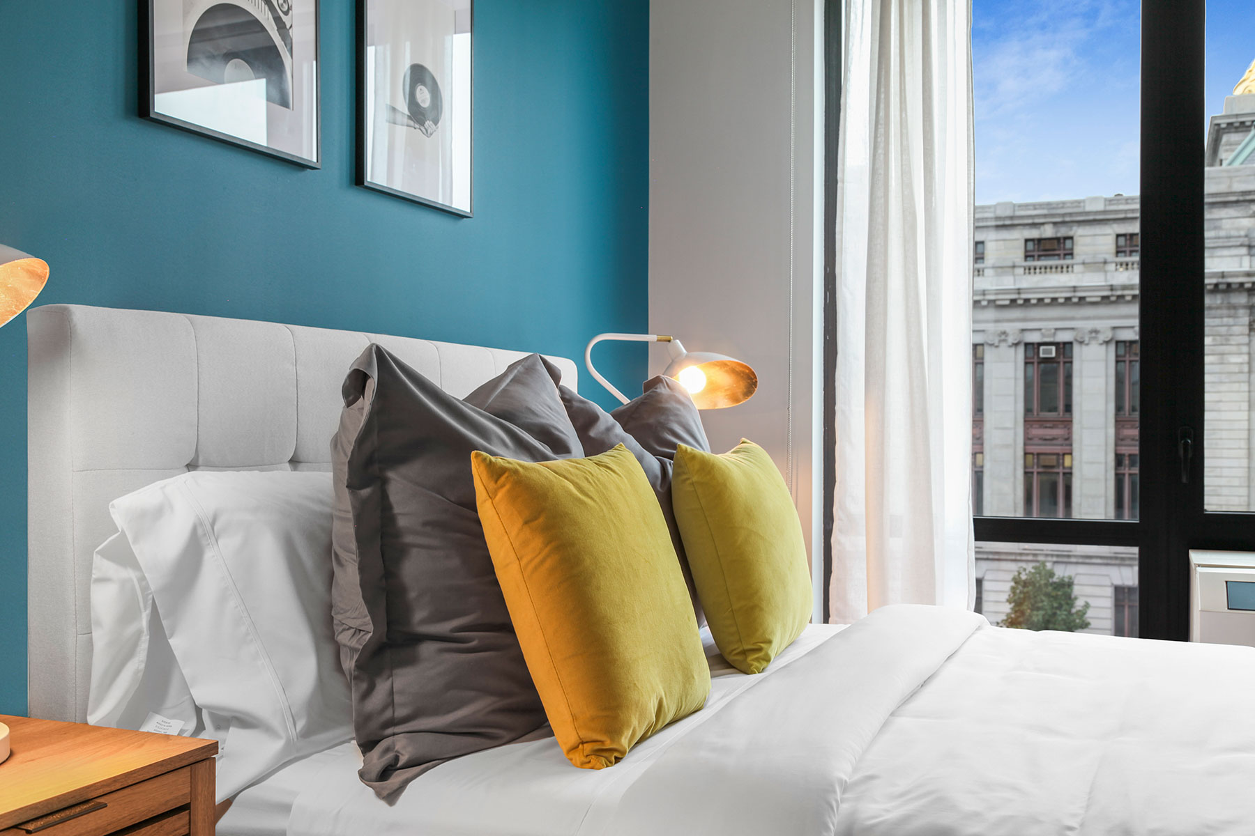 Detail of bed with modern bedding, fabric headboard, teal accent wall, and window