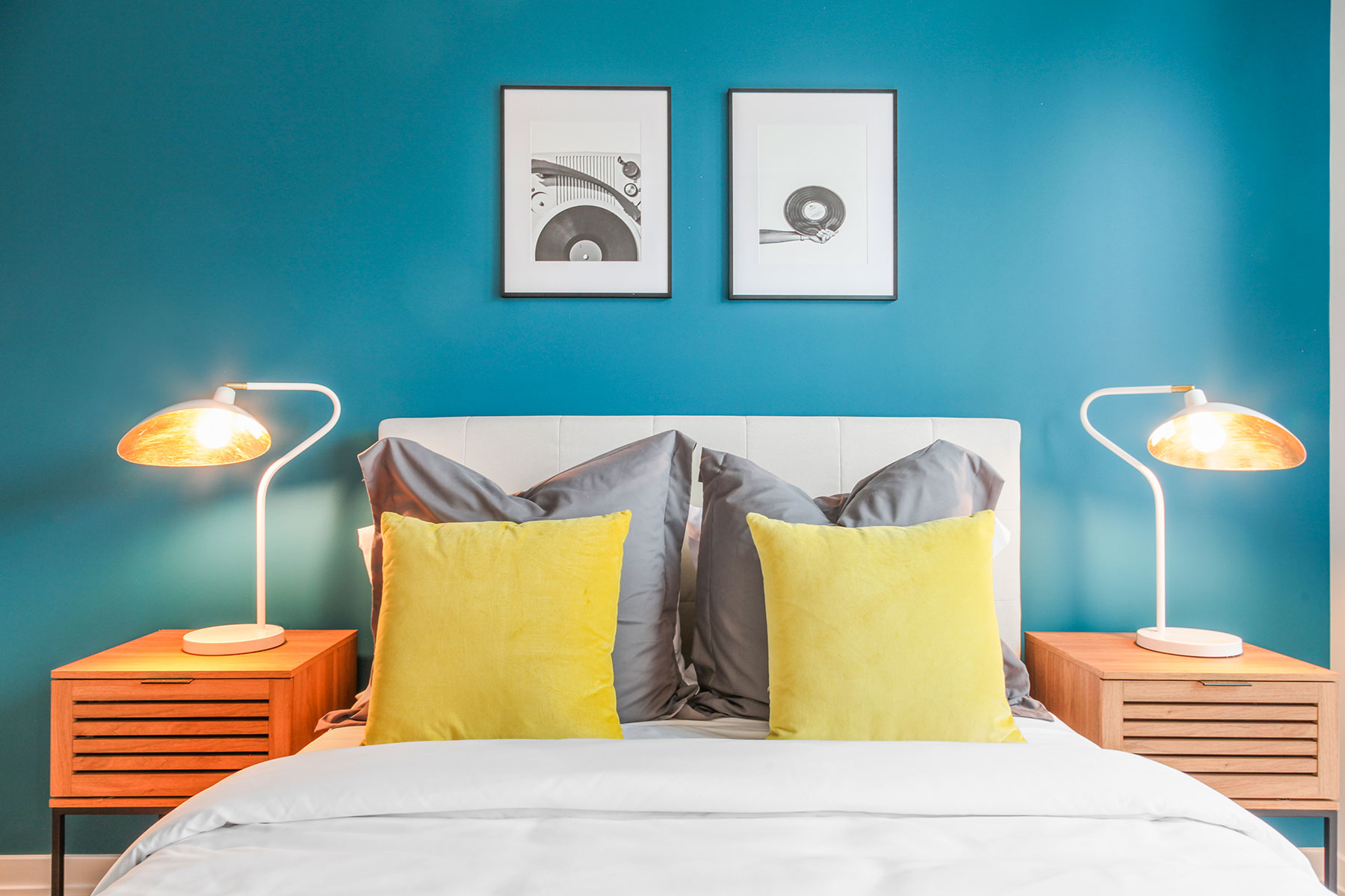 Detail of bed with modern bedding, accent pillows, fabric headboard, teal accent wall with framed art, matching wood and metal nighstands with lamps on each side