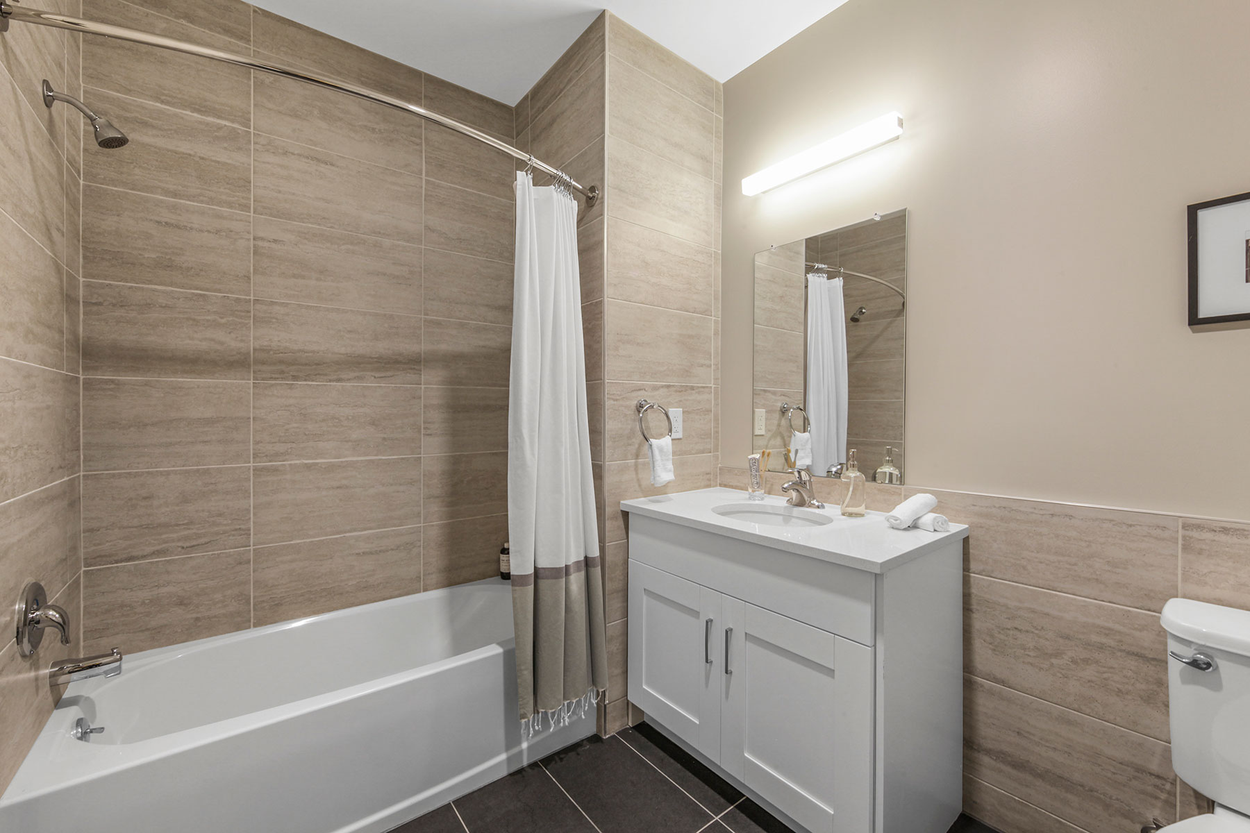 Modern bathroom with double cabinet white vanity, fully tiled tub shower, tiled floor and tiling halfway up wall
