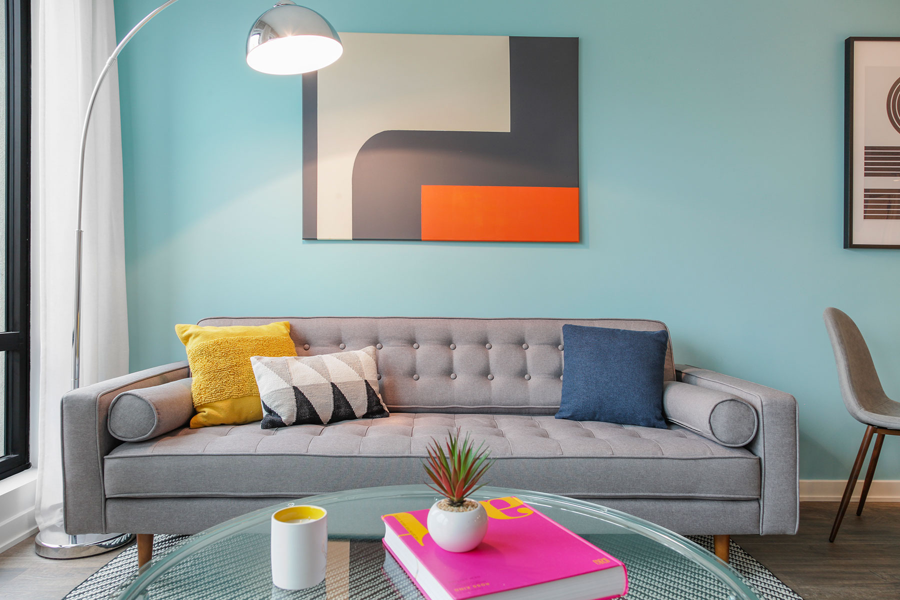 Detail of couch in living room with accent pillow modern art above on light teal accent wall, glass coffee table and lamp in corner